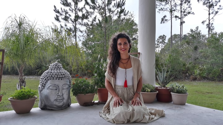 An image of Dass Shanti kneeling on a porch next to a Buddha with trees in the background.