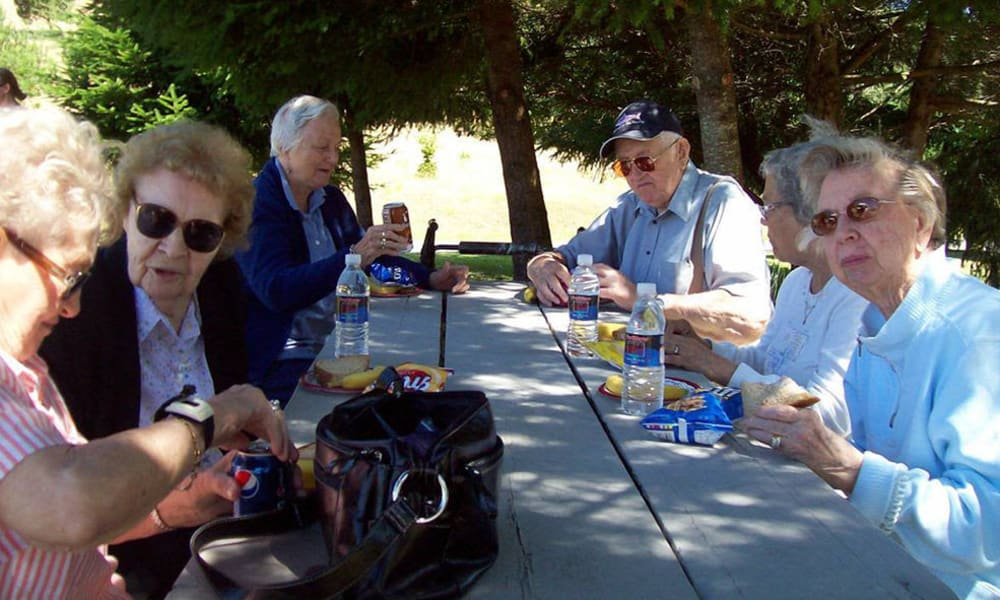 A group of residents sitting outside at Bayberry Commons in Springfield, Oregon