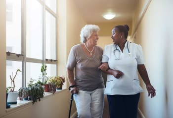 Resident taking a walk with a nurse at Discovery Village At Dominion in San Antonio, Texas