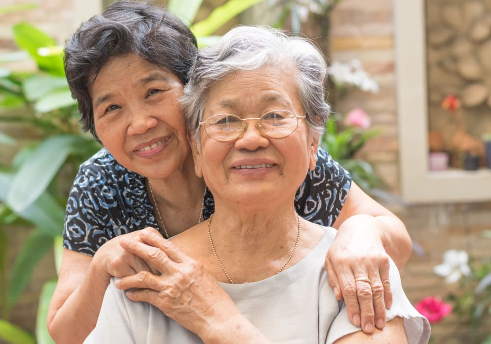 Resident friends hugging at Bridgeport Place Assisted Living in University Place, Washington.