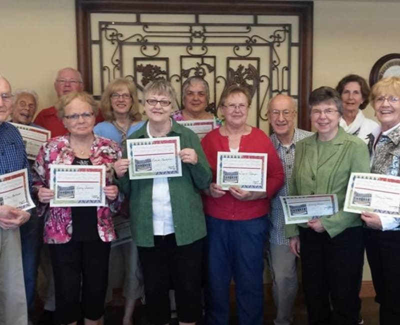 Group of residents smiling in a row at Deer Crest Senior Living in Red Wing, Minnesota