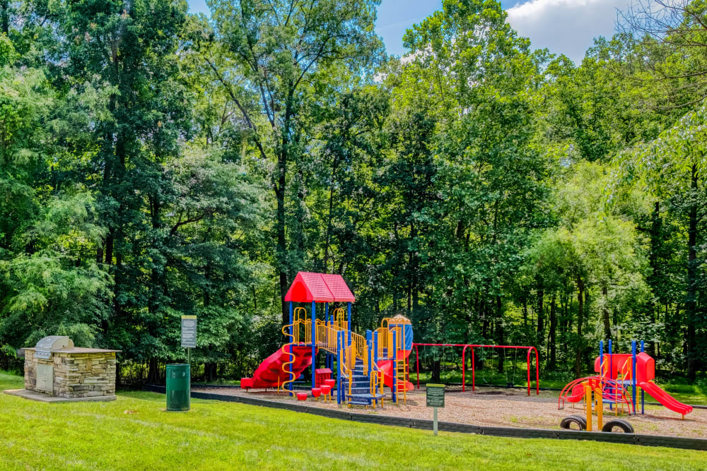 Playground in lush green landscaping at Park at Winterset Apartments in Owings Mills, Maryland