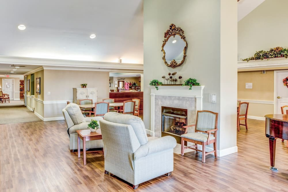 Elegant white walled living room area with tract lighting, armchairs, and fireplace at Carriage Court of Washington Court House in Washington Court House, Ohio