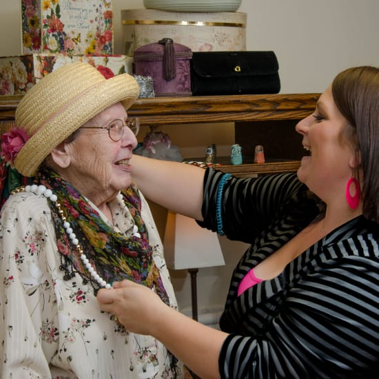 Staff helping a resident try on jewelry at Madonna Gardens in Salinas, California