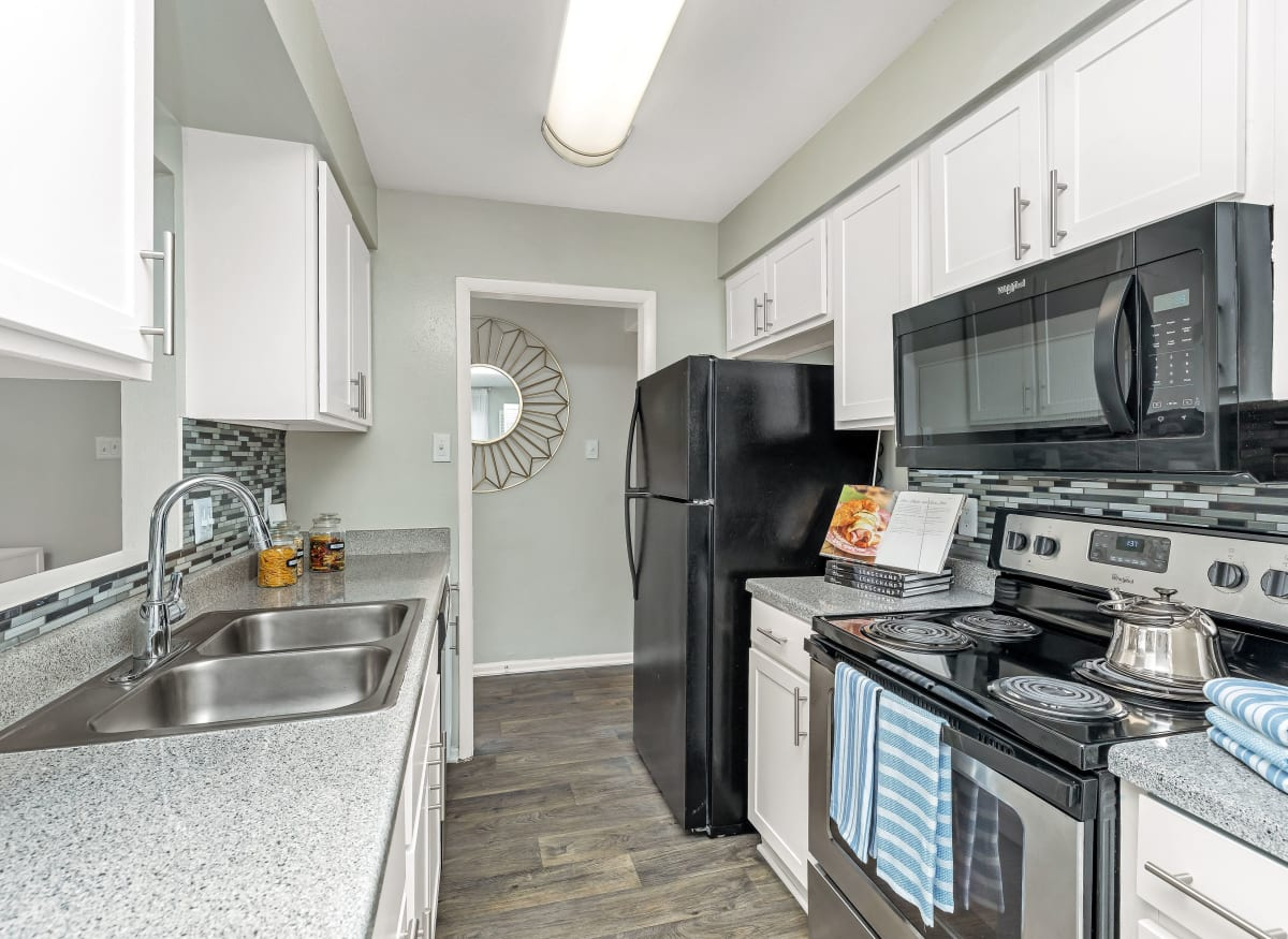 Spacious kitchen with a microwave in model apartment home of Barringer Square in Webster, Texas