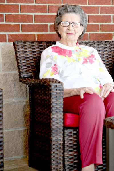 A resident sitting on a chair outside at Providence Assisted Living in Clarksville, Arkansas.