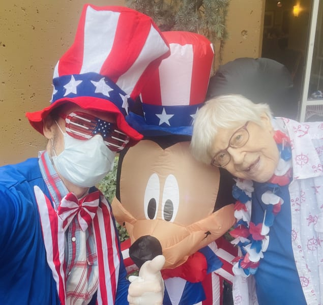 A First Hill (WA) team member and resident pose next to the Fourth of July Mickey Mouse.