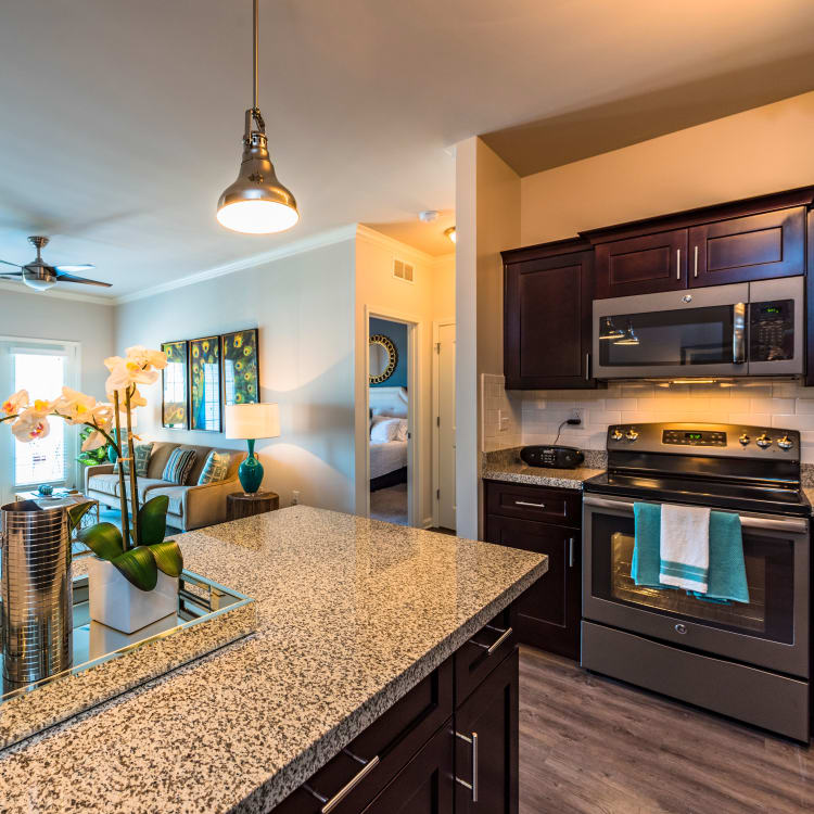 Partial view of kitchen and living area in open-concept floor plan of model home at Valley Farms in Louisville, Kentucky