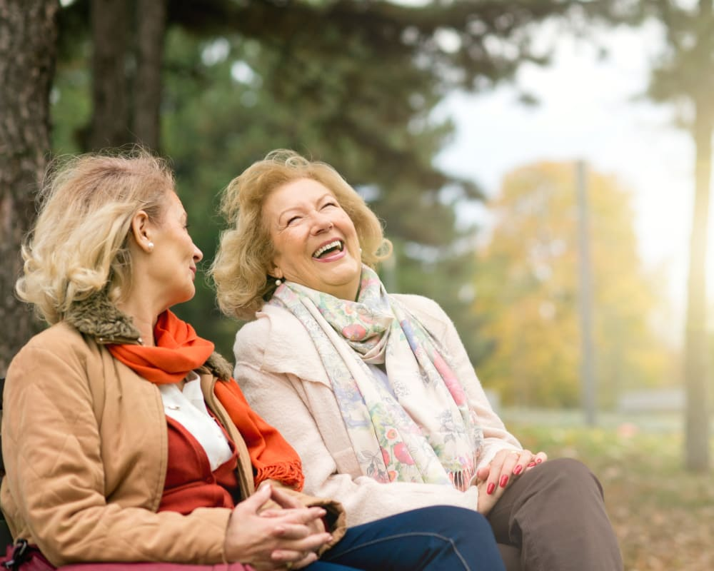 Smiling seniors laughing and enjoying the outdoors at Maplewood at Weston in , Massachusetts