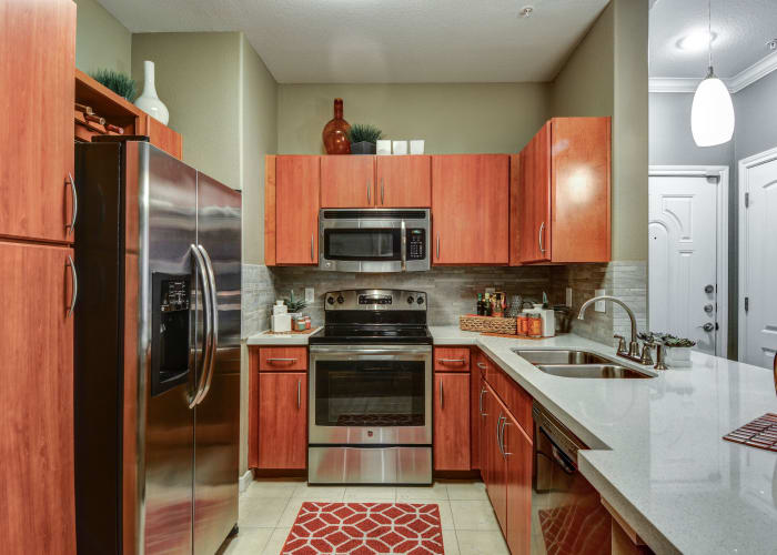 Gourmet kitchen with cherry wood cabinetry and stainless-steel appliances in model home at San Paloma Apartments in Houston, Texas