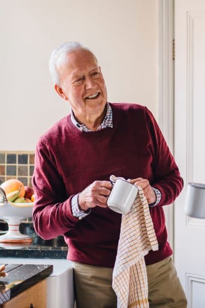 Resident Cleaning a cup in his apartment at Quail Park at Shannon Ranch in Visalia, California