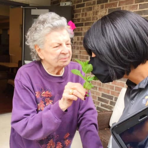 Smiling sharing a flower with caretaker at Oxford Glen Memory Care at Grand Prairie in Grand Prairie, Texas