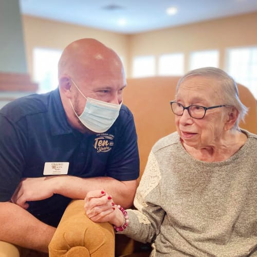 Resident with masked caretaker at Oxford Glen Memory Care at Carrollton in Carrollton, Texas