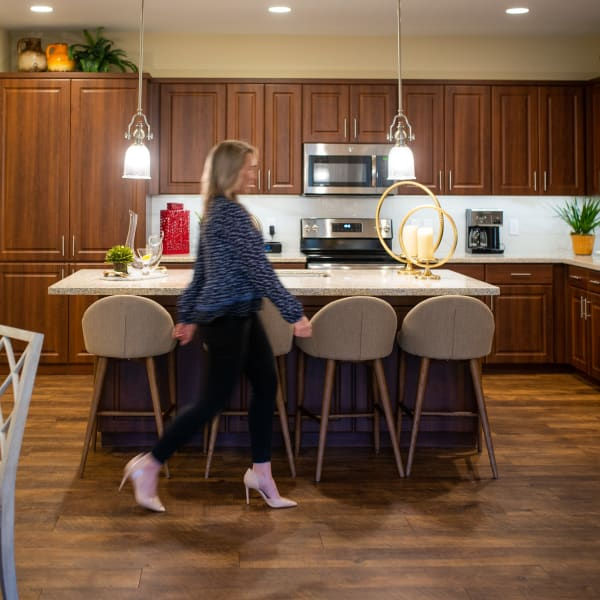 Resident walking through the gourmet kitchen in her new home at San Privada in Gilbert, Arizona