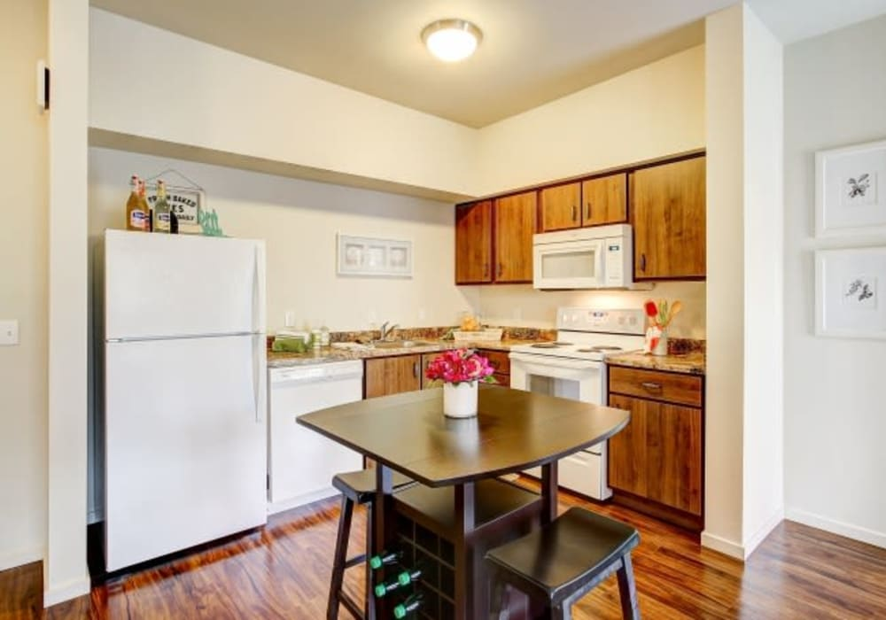 Spacious kitchen with white appliances and wooden cabinetry at LARC at Olympia in Olympia, Washington