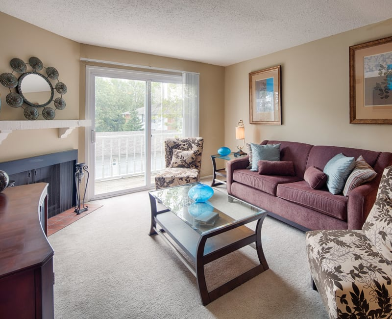 Well-furnished living area with a fireplace looking out onto the private balcony of a model home at Oxford Hills in St. Louis, Missouri
