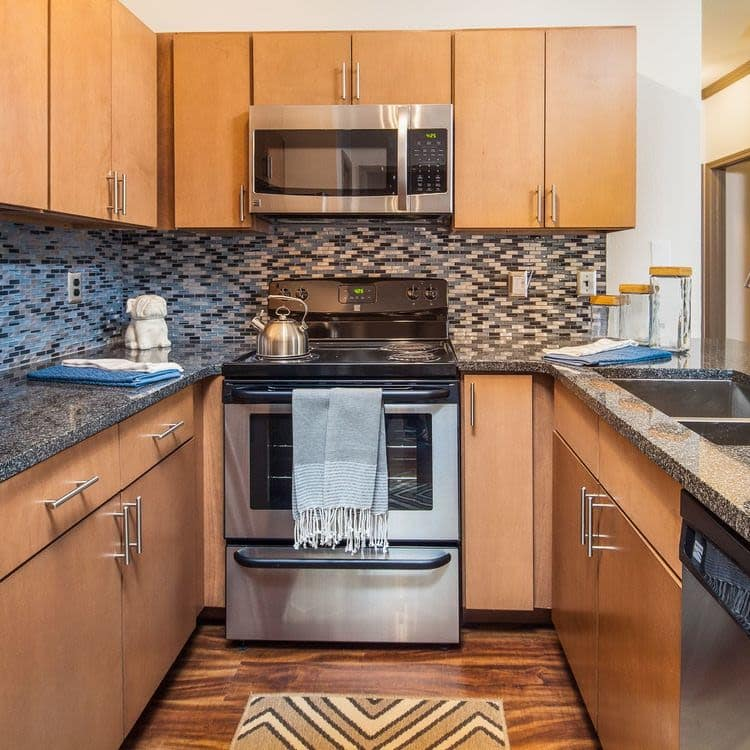 Modern kitchen with granite-style countertops and stainless-steel appliances in model home at Presley Oaks in Charlotte, North Carolina