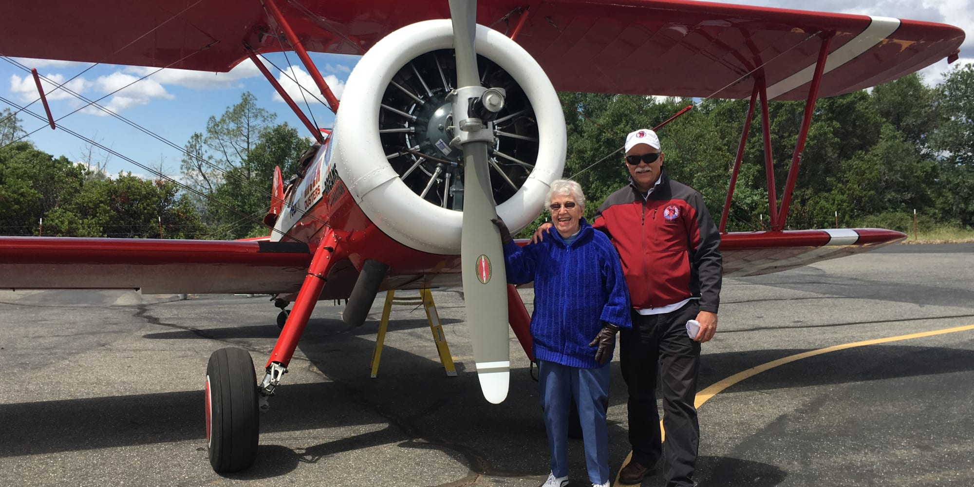 Residents of Alexis Estates Gracious Retirement Living pose by an airplane in Allen, Texas