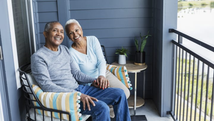 Man and woman moving into senior living and sitting on balcony