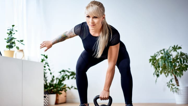 Woman with long hair in black athletic clothing leaning over a kettlebell in a sunlit interior with green plants in the background