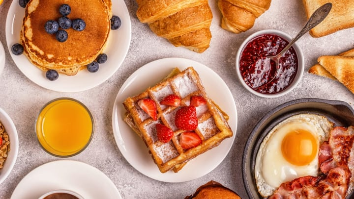 Aerial view of a collection of breakfast/brunch food on a table with a white table cloth.