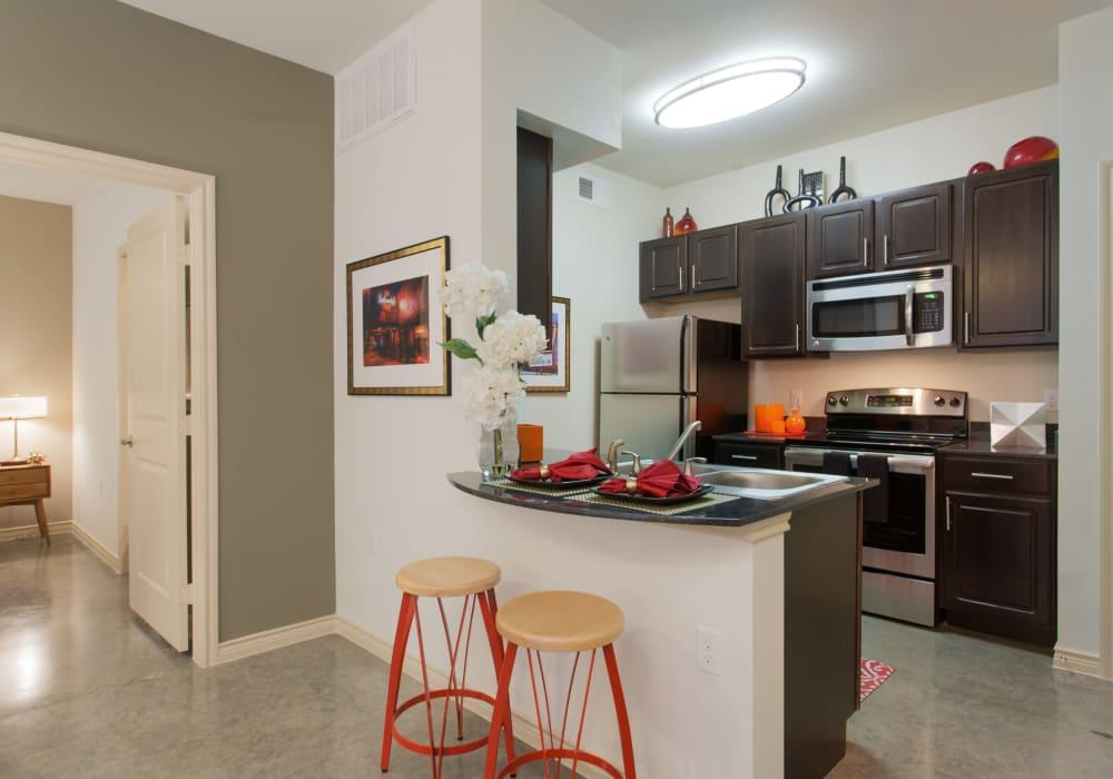 Enjoy a modern kitchen with breakfast bar at Ethos Apartments in Austin, Texas