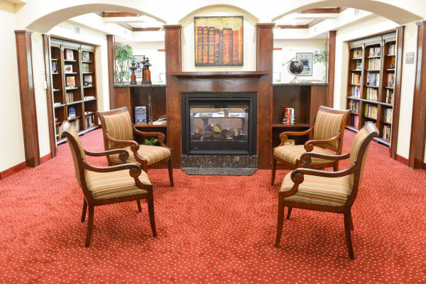 Fireside seating in the library at Ashton Gardens Gracious Retirement Living in Portland, Maine