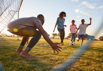 Parents helping their kids brush up on their soccer skills after school near Walden Pond in Houston, Texas