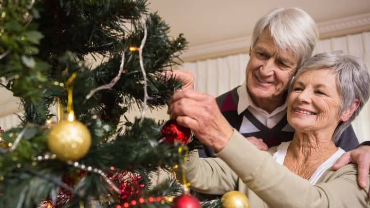 Image of an older couple decorating a Christmas tree.
