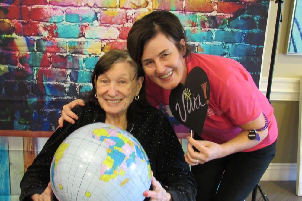senior resident holding up a globe
