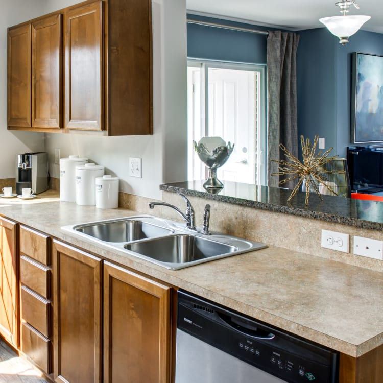 Modern kitchen with granite countertops and a breakfast bar in a model home at Sofi at Cedar Mill in Portland, Oregon