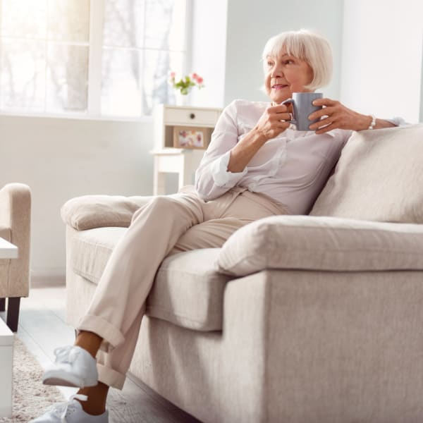 Resident enjoying a coffee in her living room at WellQuest of Granite Bay in Granite Bay, California