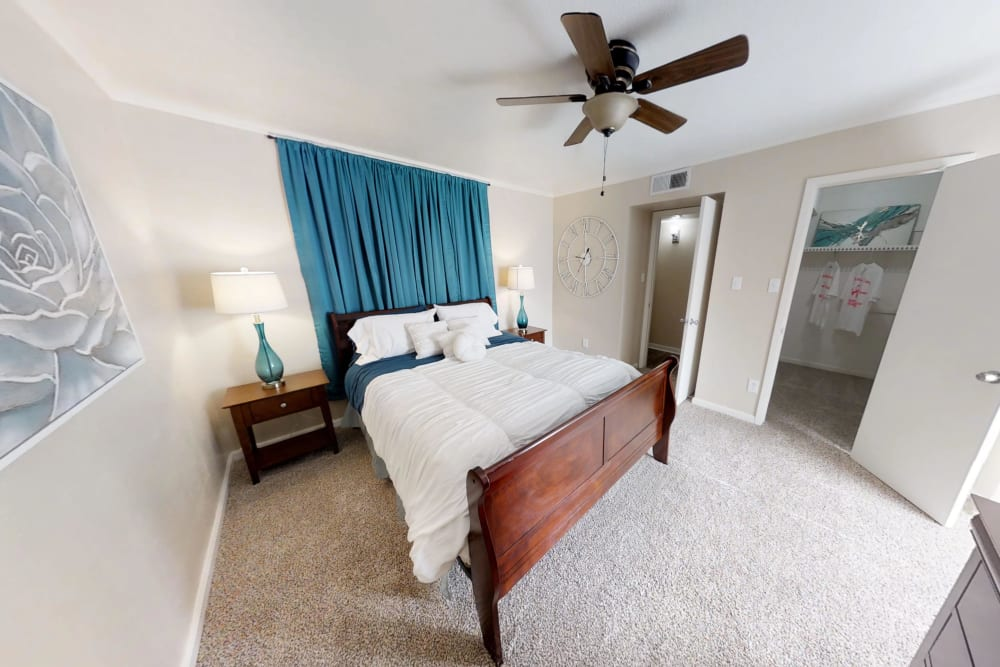 Bedroom with a ceiling fan at Falls of Maplewood Apartments in Houston, Texas