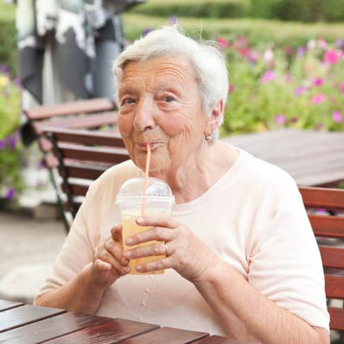 A resident drinking a milkshake at Avenir Memory Care Westside in Los Angeles, California.