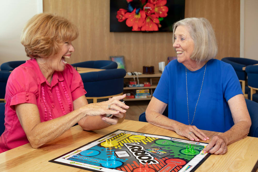Two residents playing a board game at Clearwater at Riverpark in Oxnard, California