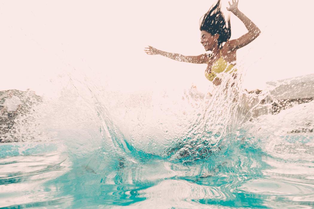 Woman jumping in the pool at Portofino Apartments in Wichita, Kansas