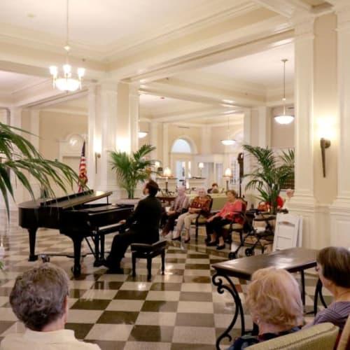 Residents enjoying a man play the piano at The Chamberlin in Hampton, Virginia