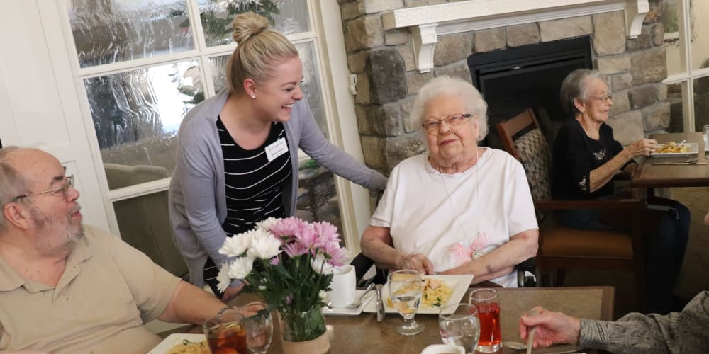 Residents dining with caregiver in background at The Springs at Grand Park in Billings, Montana
