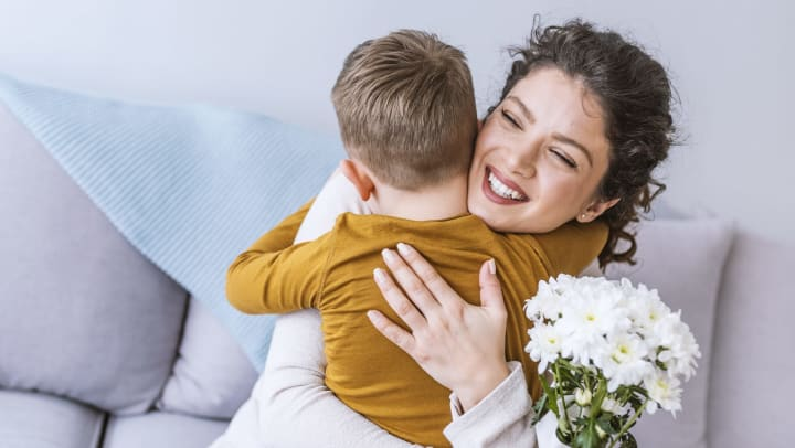 Young boy hugging an adult woman who is smiling and holding a bouquet of white daisies.