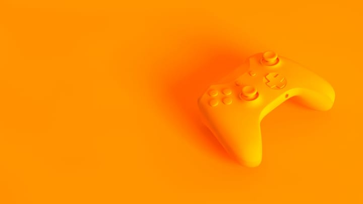 Yellow/orange generic video game controller on matching background