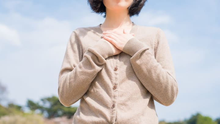 Woman with her hands over her heart in a symbol of gratitude