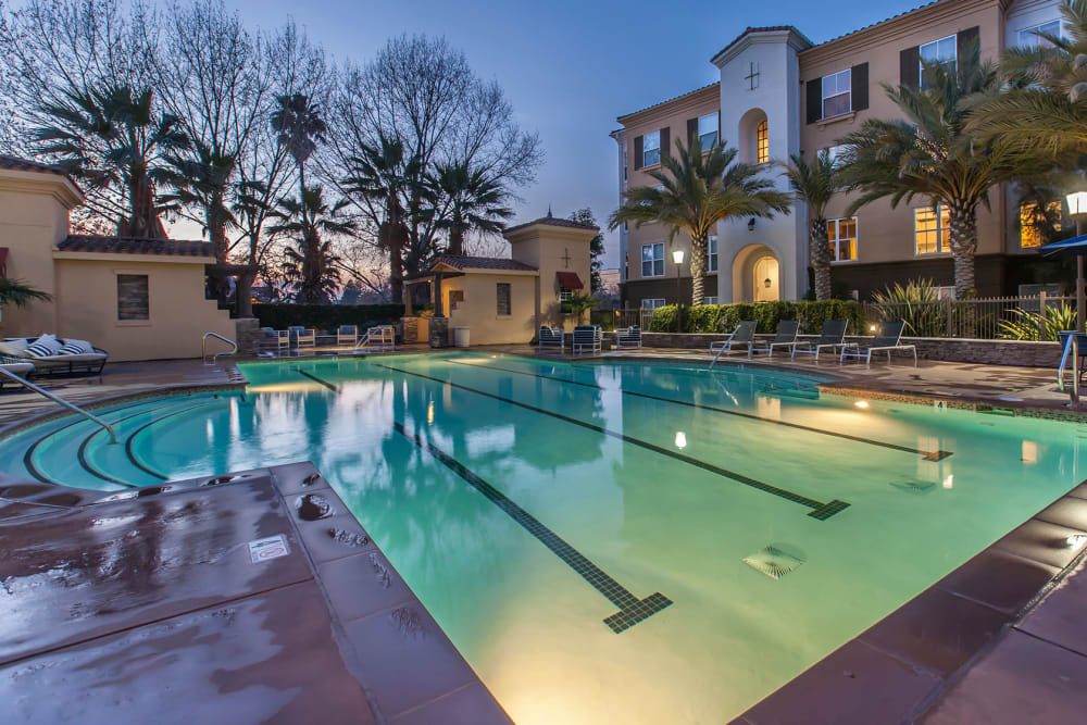Spacious sundeck with table and chairs next to a swimming pool at Park Central in Concord, California