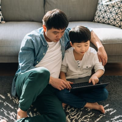Father and son looking something up online in their apartment at Haven Apartment Homes in Kent, Washington
