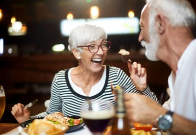 Resident couple eating dinner at a restaurant near 8500 Harwood Apartment Homes in North Richland Hills, Texas