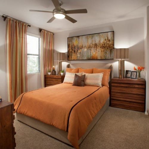 Well-furnished model home's master bedroom with a ceiling fan and plush carpeting at Vive in Chandler, Arizona