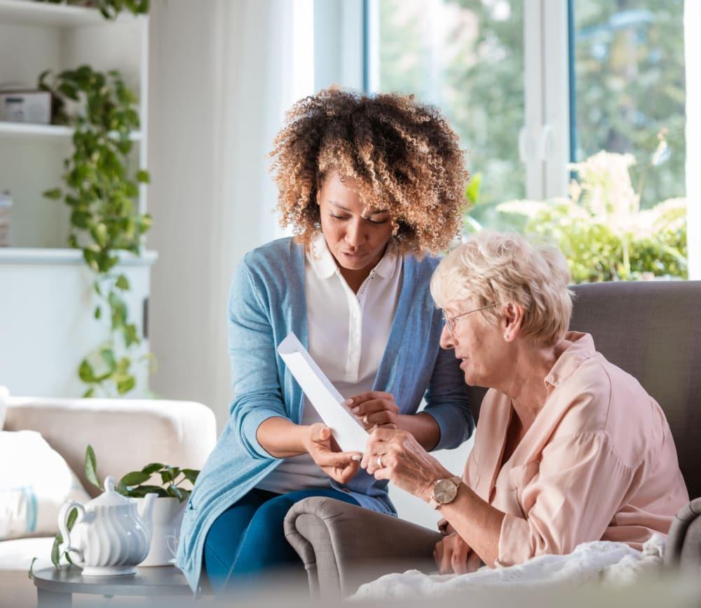 Woman reading with caregiver at Clearwater at North Tustin in Santa Ana, California.