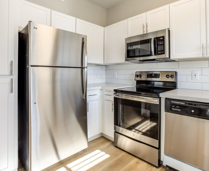 Renovated kitchen with stainless-steel appliances and a subway tile backsplash in an apartment home at Finisterra in Tempe, Arizona