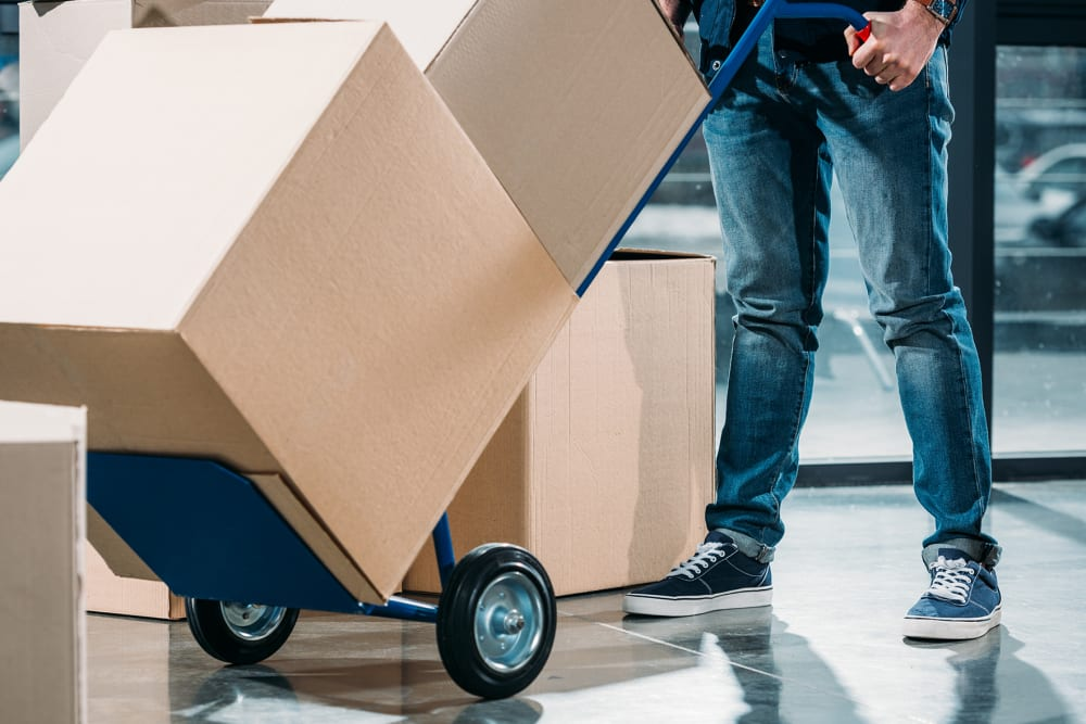 Man pushing boxes on a dolly at A-American Self Storage in Rialto, California