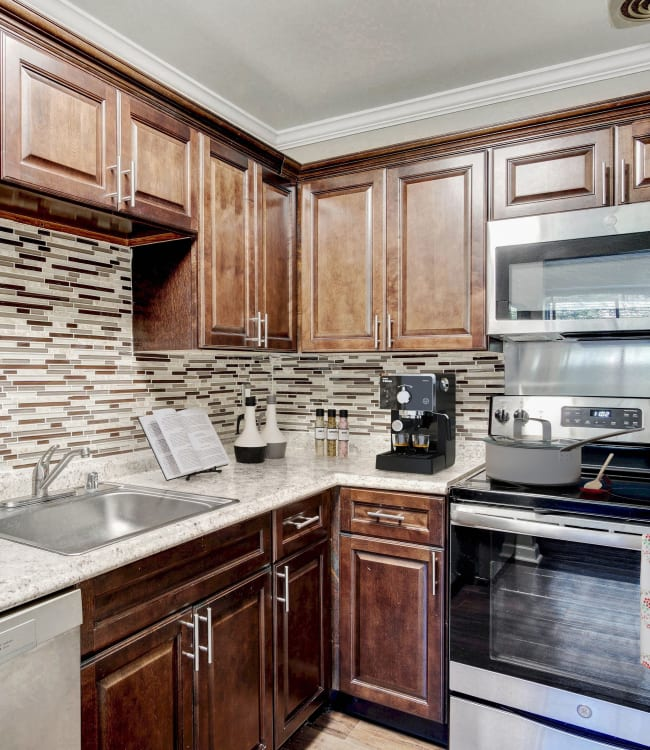 Modern kitchen with light wood cabinetry and custom tile backsplash in a model home at Heritage at Shaw Station in Washington, District of Columbia