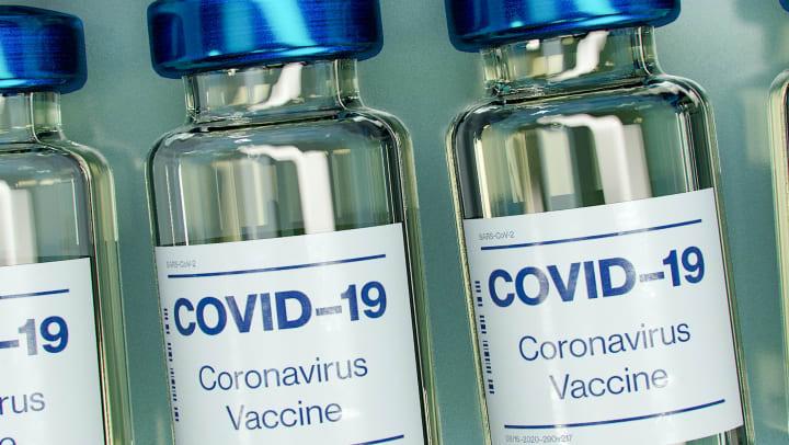 covid-19 vaccine vials in a row on blue countertop